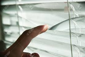 someone looking out of window opening blinds stock photo picture