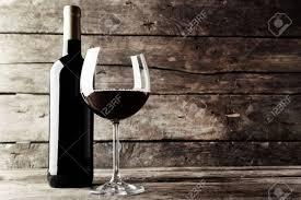 sur la table wine glasses bouteille de vin rouge et un verre sur la table en bois noir et
