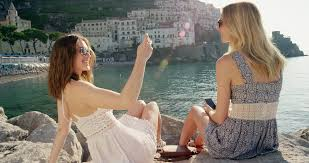 Tourist woman taking photo of best friend two travel girls sitting