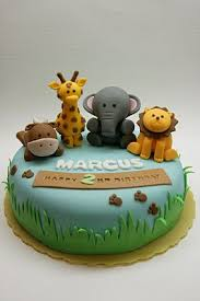 zoo themed birthday cake this cake with grass and banner and footsteps sitting zebra on top
