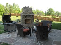outdoor fireplace with chairs on flagstone