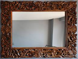 carved wood framed wall a bigger mirror green notebook