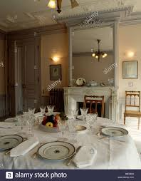 white linen cloth and napkins with place settings on dining table