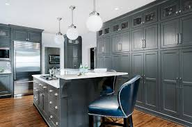dark gray center island with deep blue leather counter stools