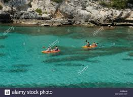 kayaking in clear blue sea water cala galdana menorca spain stock