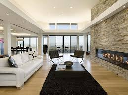 black rug open floor plan white leather sofa stone fireplace glass