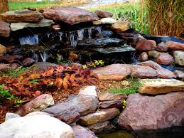 water feature with rocks ornamental plants and flowing waterfall