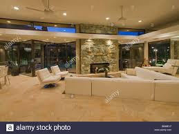 living room with white sectional sofa walls of glass and river