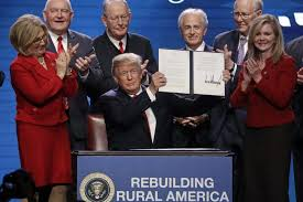 bureau r up president donald holds up an executive order after signing it