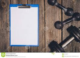workout plan background dumbbells on wooden gym floor or table