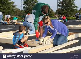 mother and children volunteer people building a house wall panel