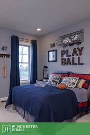 grey and red bedroom theme for a rock and roll bedroom theme i like the wall basket for assorted balls floor length blue curtains and red and navy bedding this newport model bedroom is the perfect backdrop for a
