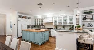 white shaker kitchen cabinets with ventahood and brick backsplash