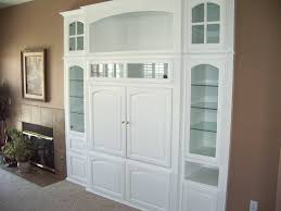 white entertainment center with glass shelves cabinet
