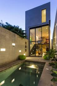 two story glass wall makes narrow mexican home feel huge http