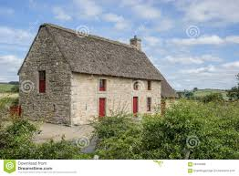 english stone cottage with a thatch roof stock photo image 58104089