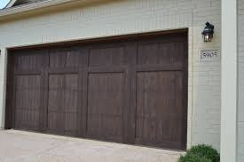 village homes wood cedar garage door stained in a dark brown a