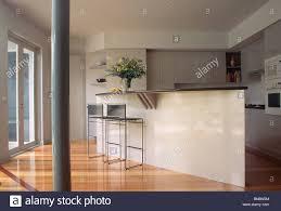 modern open plan kitchen narrow pillar and wooden flooring in modern open plan kitchen with