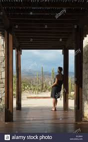 woman standing at the entrance of a small hotel in the coast of
