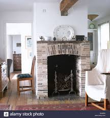 white loose cover on chair beside central fireplace with stone