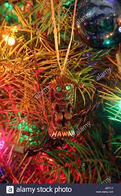 hawaiian tiki christmas ornament hanging on christmas tree stock