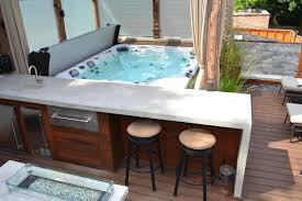 tub on deck and outdoor summer kitchen with bar space