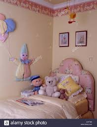 children u0027s bedroom with wallpaper frieze and toys on bed with pink