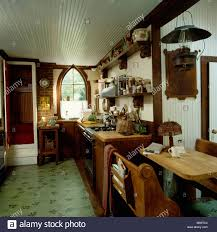 small pine table and chairs in country kitchen with green flooring
