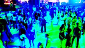 night club dance floor full of dancing people and disco lights