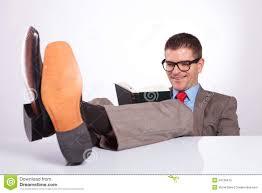 le de bureau sur pied le homme d affaires lit un livre avec des pieds sur le bureau