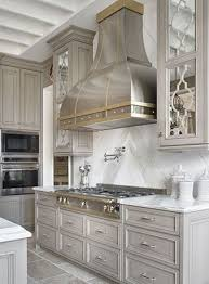 gorgeous grey washed kitchen and stainless hood with brass details