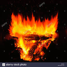 close up of a roaring wood fire burning with glowing embers in the