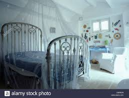 white mosquito net above white antique wrought iron bed in greek