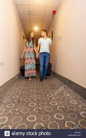 young couple room young couple standing at hotel corridor upon arrival looking for