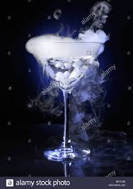 martini photography exotic drink in a martini glass with smoke coming out of it stock
