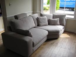 a small room with a bay window takes a large sofa section this