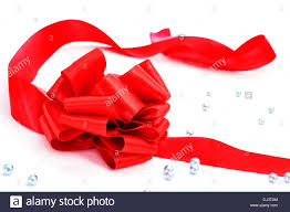 a ribbon with a bow and some small silver balls on a white