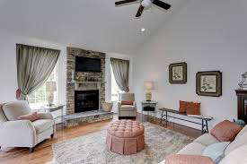 cute cozy sitting area with stone fireplace high vaulted ceiling
