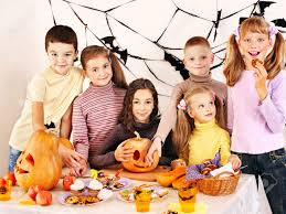 family on halloween party with children making carved pumpkin