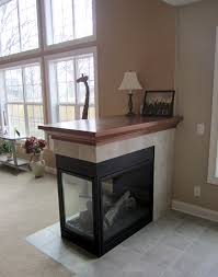 three sided fireplace with tile surround and oak mantle top the