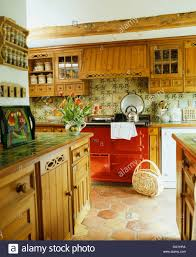 fitted oak units with green tiled worktops in country kitchen with
