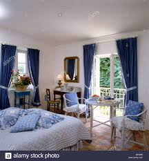 blue cushions piled on bed in country bedroom with blue curtains