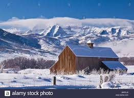 old barn in foreground of a beautiful winter landscape with