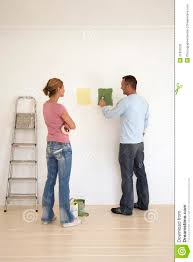 woman watch man testing paint colors on wall stock photo image