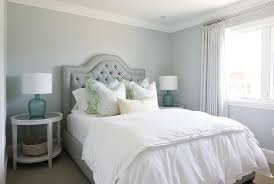 gray tufted bed with round whitewashed nightstands with mirror