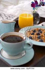 breakfast in bed with coffee granola and yogurt orange juice and