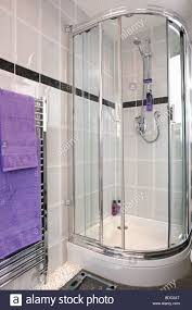 corner shower cabinet with glass doors in modern grey tiled