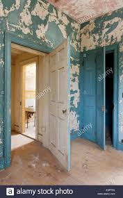 open door in room with cracked and peeling wall paint stock photo
