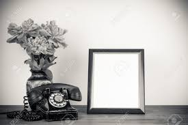 vintage old telephone frame and flowers on table sepia photo