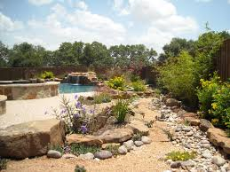 native pond plants native landscaping around a pool with tub and outdoor kitchen